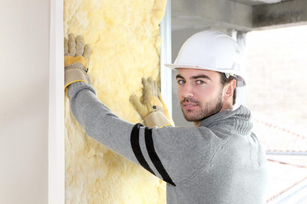 male worker putting insulation