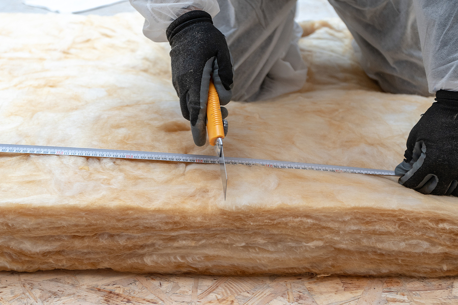 worker in overalls working with rockwool insulation, cutting material, using knife tool and measuring tape, sitting inside new house under construction