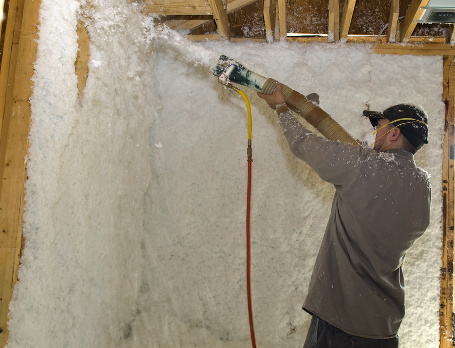 male worker blowing insulation into the wall